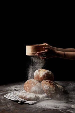 cropped shot of female baker sieving flour over various types of bread on sackcloth isolated on black background