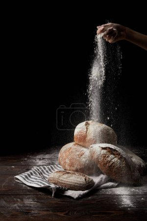 partial view of female baker sieving flour over various types of bread on sackcloth isolated on black background