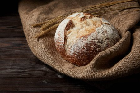 closeup image of bread, wheat and sackcloth on rustic wooden table