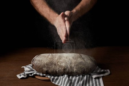 cropped shot of male baker clapping hands with flour over bread on sackcloth