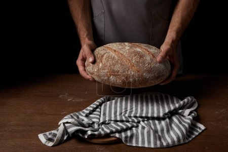 partial view of male baker in apron holding bread over wooden table