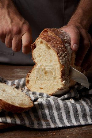 Photo for Cropped shot of male baker cutting bread by knife on sackcloth on wooden table - Royalty Free Image