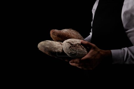cropped image of male baker in apron holding various types of bread isolated on black background
