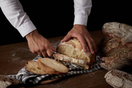 partial view of male baker cutting bread by knife on sackcloth on wooden table