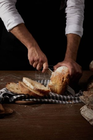 partial view of male baker in apron cutting bread by knife on sackcloth on wooden table