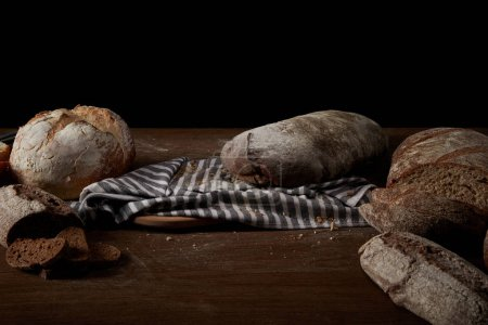 close up view of various types of bread, sackcloth and cutting board on table