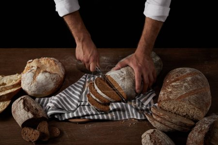 cropped image of male baker cutting bread by knife on sackcloth on wooden table