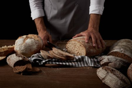 Photo for Cropped image of baker in apron cutting bread on sackcloth on wooden table - Royalty Free Image