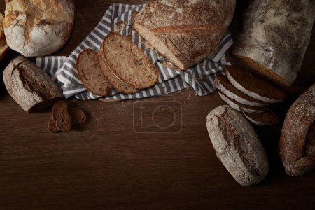 top view of various types of bread and sackcloth on wooden table