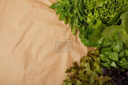 top view of fresh various leaf vegetables on crumpled paper