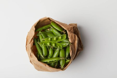 top view of ripe pea pods in paper bag on white surface