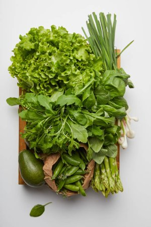 top view of various ripe vegetables in box on white surface