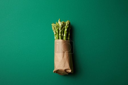 top view of bunch of ripe asparagus covered with kraft paper on green surface
