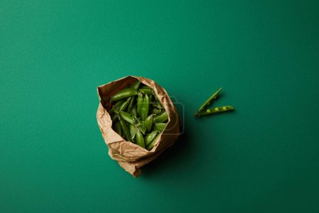 top view of paper bag with pea pods on green surface