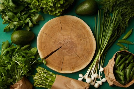 top view of wood cut surrounded with various ripe vegetables on green surface