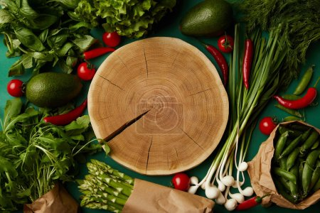 top view of wood cut surrounded with different ripe vegetables on green surface