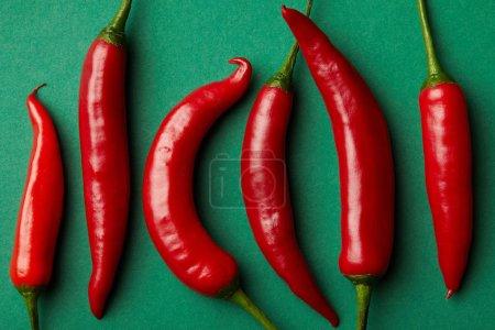 Photo pour Vue du dessus des piments rouges en rangée sur la surface verte - image libre de droit