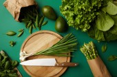 top view of different ripe vegetables with wooden cutting board and knife on green surface