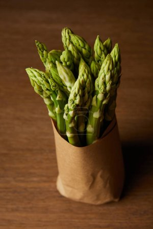 close-up shot of bunch of asparagus covered with kraft paper on wooden surface