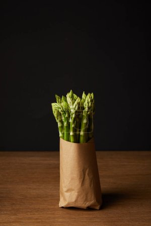 close-up shot of bunch of ripe asparagus covered with kraft paper on wooden surface