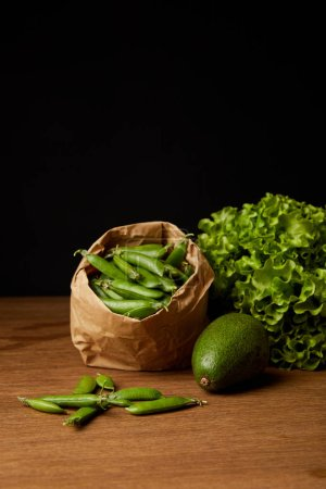 close-up shot of avocado, green peas and lettuce on wooden surface