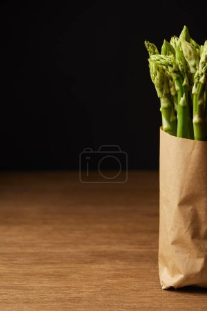 cropped shot of bunch of ripe asparagus covered with kraft paper on wooden surface