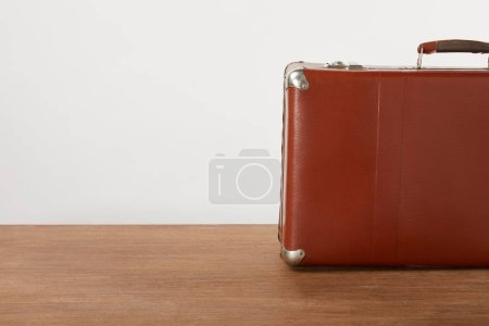 Vintage leather suitcase on wooden table by white wall