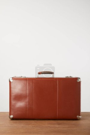 Photo for Closed leather suitcase on wooden background - Royalty Free Image