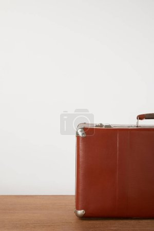 Brown vintage suitcase on wooden table by white wall