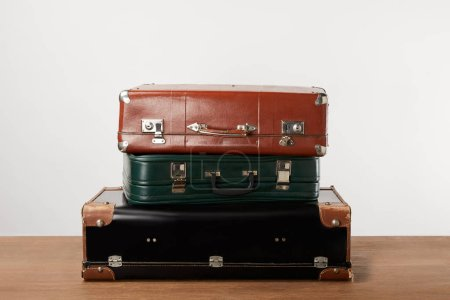 Photo for Stacked old leather travel bags on wooden table - Royalty Free Image