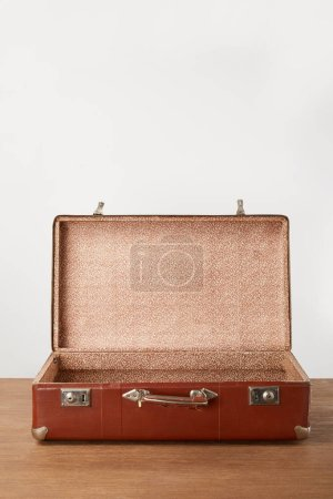 Photo pour Vieille valise vide brune ouverte sur table en bois - image libre de droit