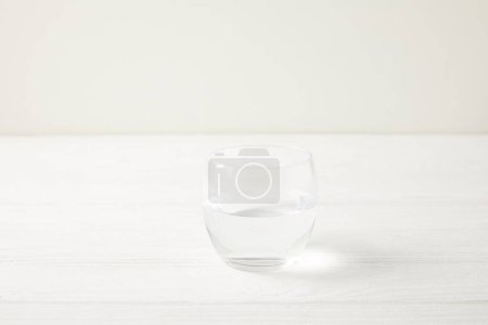 close-up shot of single glass of water on white wooden tabletop