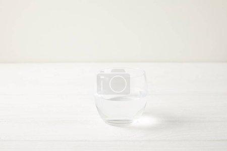 Photo pour Gros plan tiré du simple verre d'eau sur une table en bois blanche - image libre de droit