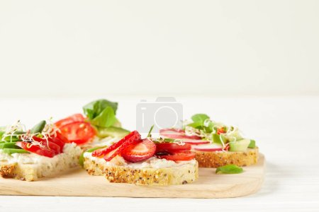 various fresh sandwiches on cutting board and on white surface