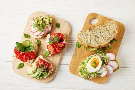 Photo pour Vue de dessus de divers sandwiches délicieux sur une table en bois blanche - image libre de droit