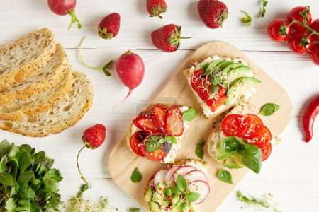 top view of tasty sandwiches on cutting board surrounded with ingredients on white wooden surface
