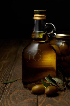bottle of aromatic olive oil with branch and jar on wooden table