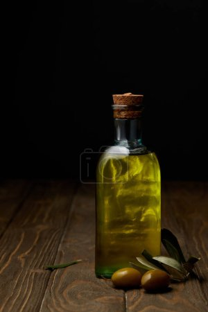 bottle of delicious olive oil with branch on wooden surface