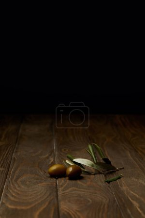 olive branch with olives on wooden surface
