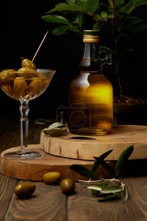 Olivenöl in der Flasche mit Oliven im Vintage-Glas auf gestapelten Brettern