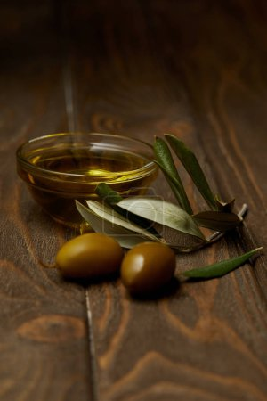 close-up shot of olive oil with branch of olives on wooden surface