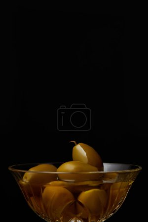 olives in bowl with oil isolated on black