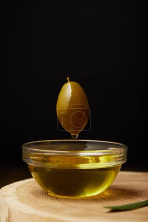 olive flying above bowl with oil on wooden surface