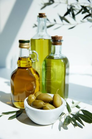 various bottles of aromatic olive oil, bowl with green olives and branches on white table