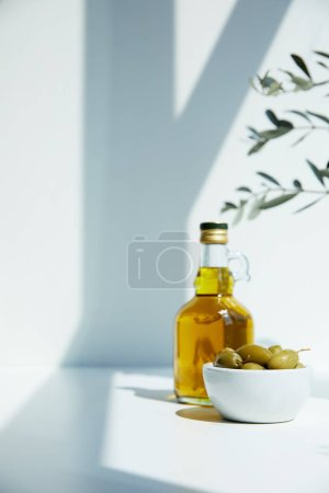 bottle of aromatic olive oil with branches and bowl with green olives on white table
