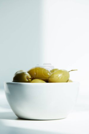 bowl with green olives on white table