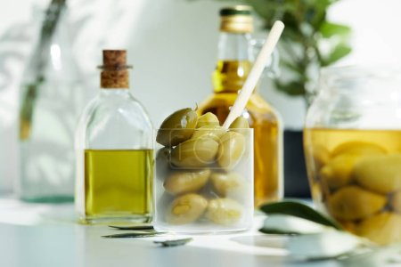 glass with spoon and green olives, jar, various bottles of aromatic olive oil with and branches on white table