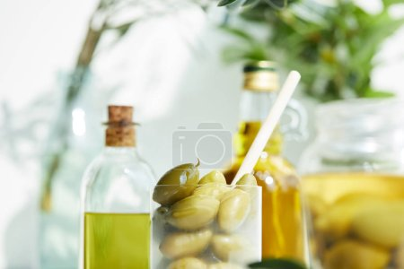 closeup shot of glass with spoon and green olives, jar, various bottles of aromatic olive oil with and branches on wooden tray