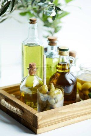 Glas mit Löffel und Oliven, Glas, verschiedene Flaschen aromatisches Olivenöl mit und Zweige auf Holztablett
