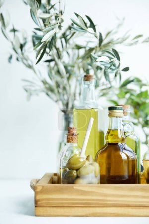 glass with spoon and green olives, various bottles of aromatic olive oil with and branches on wooden tray